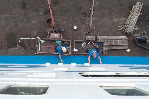 Men painting her blue stripe